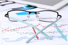 Glasses lying on a business graph analysis report. Royalty Free Stock Photography