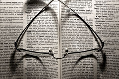 Glasses lying on a dictionary Royalty Free Stock Photo