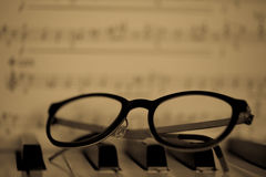 Glasses lying on piano Stock Photos