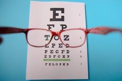 Glasses lying on snellen test chart Stock Photos