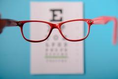 Glasses lying on snellen test chart Stock Photography