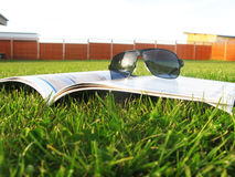 Glasses on the magazine on the grass Royalty Free Stock Images