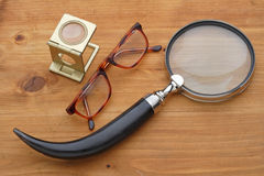 Glasses and magnifying. On wooden table stock photo
