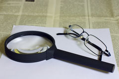 Glasses and Magnifying glass on newspaper Royalty Free Stock Photo