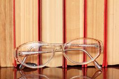 Glasses and many hardback books on wooden shelf. Education background. Library concept Royalty Free Stock Photo
