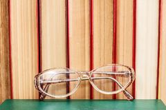Glasses and many hardback books on wooden shelf. Education background. Library concept Stock Photography