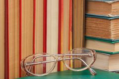 Glasses and many hardback books on wooden shelf. Glasses and many old hardback books on wooden shelf. Education background. Library concept Stock Images