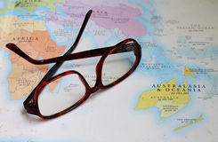 Glasses on map. Geographic book royalty free illustration