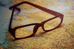 Glasses on map background royalty free stock photography