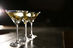 Glasses of martini cocktail with olives on bar counter. Space for text stock images