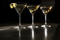 Glasses of martini cocktail with olives and lemon peel on bar counter. Space for text royalty free stock images