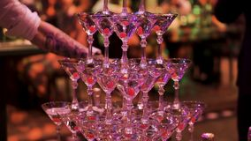 Glasses with Martini cocktail with ultraviolet color illumination. Clip. Champagne slide. Pyramid or fountain made of. Glasses with Martini cocktail with stock photo