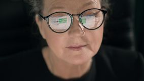 In glasses of mature woman is displaying newsline while she is looking through social media stock footage