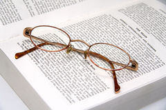Glasses on a medical book. Pair of tortoise shell style glasses on a medical book stock photo