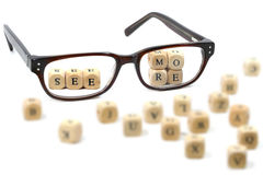 Glasses and message - see more - in wooden blocks, isolated. Glasses and message see more written in wooden blocks, isolated on white background, some blurry stock photos
