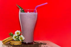 Glasses of milk cocktail with strawberry, ice cream on wooden plate and red background. Sweet drinks for summer concept. Darkened gasses of milk cocktail with Stock Photography