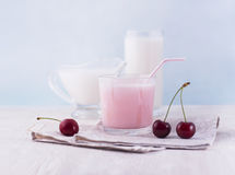 Glasses of milk and delicious milkshake and fresh berries on whi Stock Photos