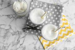 Glasses with milk shake and tasty vanilla ice cream. On light background royalty free stock photos