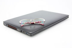 Glasses on modern laptop. Isolated over white background Royalty Free Stock Photo