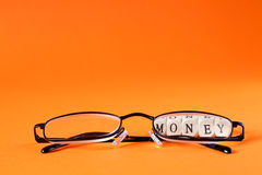 Glasses with money lettering Stock Photos
