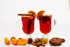 Glasses with mulled wine or hot cider near orange slices and cookies on white background. Mulled wine near slices of Stock Photos
