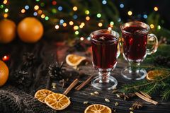 Glasses with mulled wine on a wooden table decorated with a Christmas trees. Traditional winter alcoholic drink with stock image