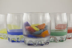 Glasses and multicolored ice. Glasses with colored ice on a white background Stock Images