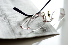 Glasses on a newspaper Stock Images