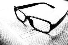 Glasses on newspaper Stock Photos