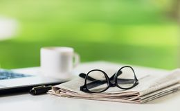 Glasses on newspaper. Break broadsheet business coffee communication computer Royalty Free Stock Photo