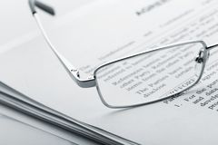 Glasses on the newspaper Stock Images