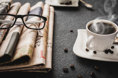 Glasses and newspaper. And cup of coffee on black stone background Royalty Free Stock Images
