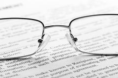 Glasses on newspaper. Macro Royalty Free Stock Photo