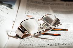 Glasses on newspaper Stock Images