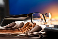 Glasses on newspapers Stock Image