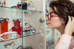Glasses always is not enough. Side portrait of good-looking modern woman in transparent glasses looking at stand with. Eyewear and picking from variety of royalty free stock photography