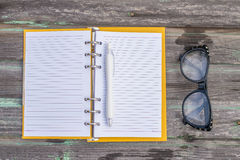 Glasses and note book. Glasses with note book on wood background Stock Images