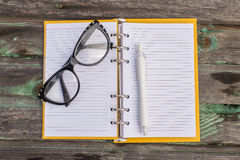 Glasses with note book. On wood background Royalty Free Stock Photos