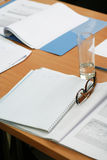 Glasses on the notebook. Empty table on seminar Royalty Free Stock Image