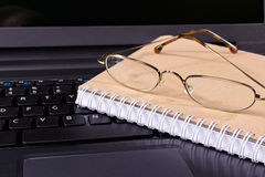 Glasses and notebook lie on the keyboard Stock Photo