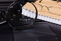 Glasses and notebook lie on the keyboard Royalty Free Stock Photography