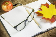 Glasses,notebook,pen and autumn leaves Royalty Free Stock Photography