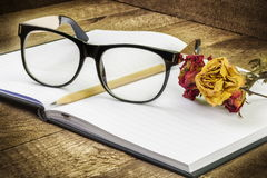 Glasses,notebook,pen and dry roses Stock Photography