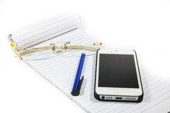 Glasses notebook pen telephone stock photo