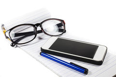 Glasses notebook pen telephone Stock Photos