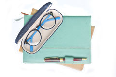Glasses on notebook. And pen on white background Royalty Free Stock Image