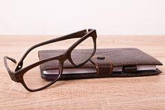 Glasses and a notebook on a table Royalty Free Stock Image