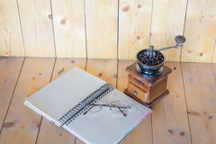 Glasses on a notebook. Vintage coffee grinder and glasses on a notebook on wooden background Royalty Free Stock Photo