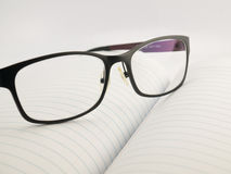 Glasses on notebook. With white background Royalty Free Stock Images