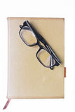 Glasses on notebook. On white background Royalty Free Stock Photography